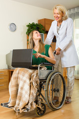 Woman and handicapped girl with laptop