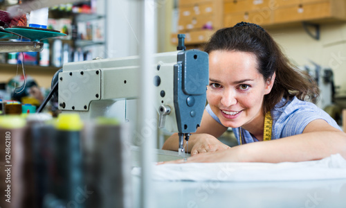 Young woman tailor working on sewing machine