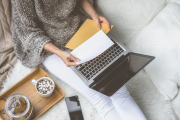 Girl in beige knit sweater and white pants sitting at home in cozy atmosphere and is holding golden envelope.In lap of girl is laptop. Girl using gadget. In the background white knitted pillow.