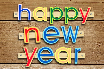 Nailed greeting text Happy New Year on brown wooden background