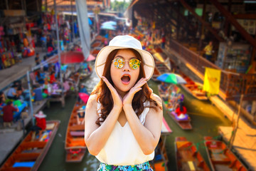 Wow. Close up portrait young asian woman beautiful girl with long red hair looking excited holding her mouth opened amazing thai culture Damnoen Saduak floating market in Ratchaburi, Thailand