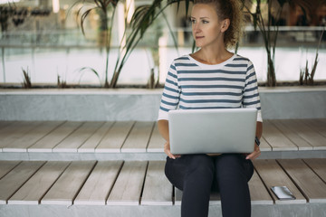 A woman in a striped blouse sits on a wooden bench, holding a laptop on her lap. Nearby is a smartphone. Girl using the gadget. Loft interior.