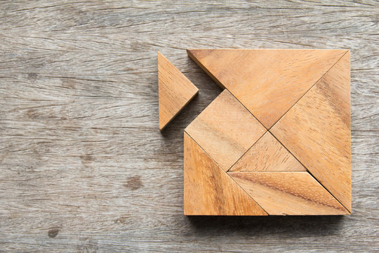 Tangram puzzle wait for fulfill to square shape on wooden table