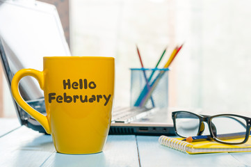Hello February written on yellow coffee cup at business office background with empty space. Winter time