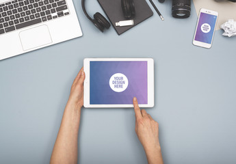 User with Tablet with Smartphone on Blue Background Mockup