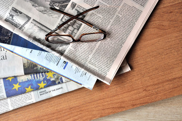 Glasses and newspapers on the desktop.