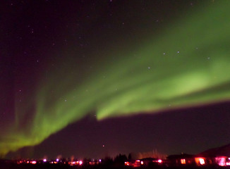 Awesome Northern Lights Swirling over a Small Town in North Iceland