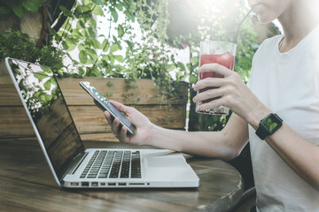 Side view of girl in white shirt sits at wooden table in cafe and uses smartphone while drinking beverage. On table is laptop, in background plants. Woman using  gadget. In female's hand smartwatch.