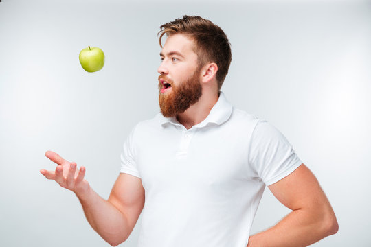 Happy casual young man throwing up an apple