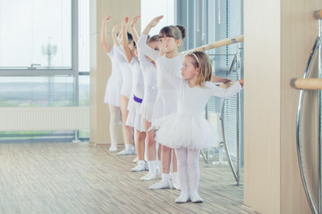Group of seven little ballerinas standing in row and practicing