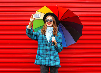 Fashion pretty young smiling woman with colorful umbrella taking