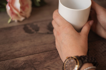 Girl is holding white cup in hands. White mug for woman, gift. Female hands with watch and bracelets holding hot cup of coffee or tea in mor