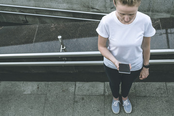 View from above.Girl in white Tshirt and blue pants stands in the city outside,while holding smartphone and looking at screen.Girl lays a route map on smartphone.Young woman uses digital gadget.Mockup