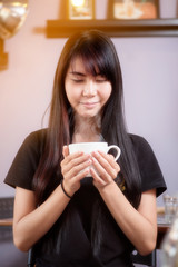 Traveler girl living happily inside a coffee shop. She inhaled the aroma of coffee in the cup.
