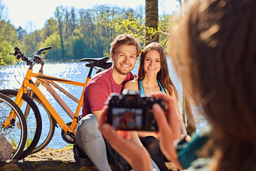 A woman taking pictures of sporty couple after bicycle ride