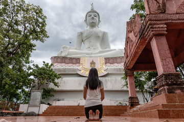 The girl was praying for blessings on a huge white Buddha.