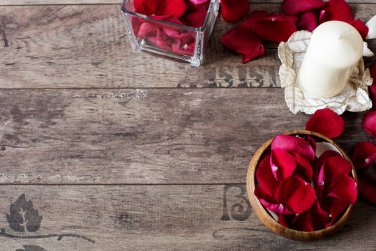 Glass vase and wood bow filled with red and white rose petals, white aromatic vanilla candle. Wooden background. Aromatherapy concept. Romantic background. Rose frame with copy space