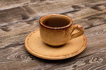Small cup of coffee on wooden background