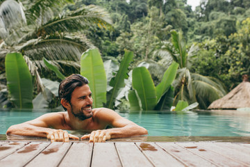 Man in pool at luxury holiday resort