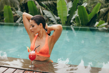 Attractive young woman in swimming pool with cocktail