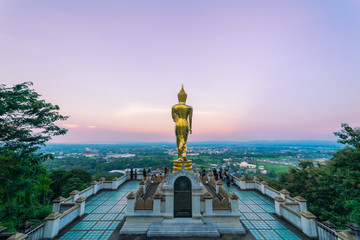 Sunset scence of Golden Buddha statue standing on a mountain Wat Phra That Khao Noi, Nan Province, Thailand