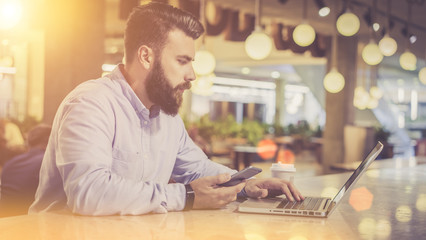 View from the side, a bearded man in a shirt using a laptop sitting at a table in a café, in a man's hand cell phone, on the table cup of coffee.Film effect, blurred background.A man checks the email.