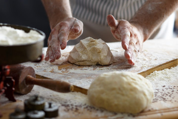 Close up of male baker hands kneading the dough with flour powder.