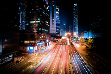 HONG KONG - JAN 23, 2015: Futuristic night cityscape view with illuminated skyscrapers and city traffic across street. Hong Kong