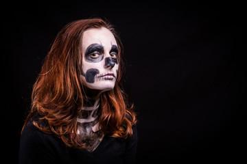 Une jeune fille rousse maquillée en squelette sur fond noir nous regarde