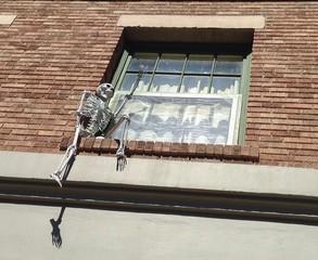 Skelett sitzt an der Hauswand vor einem Fenster