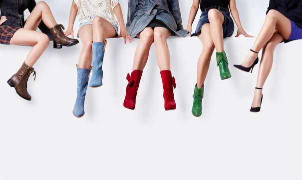Many woman with colorful shoes sitting together.Fashion shopping image.