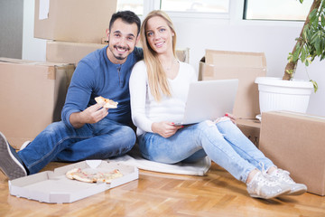Couple moving Into new home and eating pizza