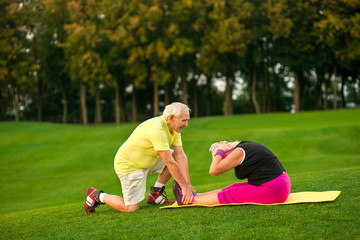 Senior woman doing physical exercise. Elderly people outdoor. Age and strength. Few sets of situps.