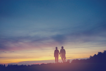 Couple on background of sunset. Woman and man holding hands. You have my heart. Uncover the secrets of life.