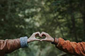 hands linked with heart sign outdoors