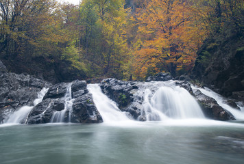 Beautiful waterfall in forest, autumn landscape with lots of red