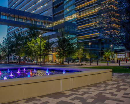 Modern office building with courtyard and water feature at night.