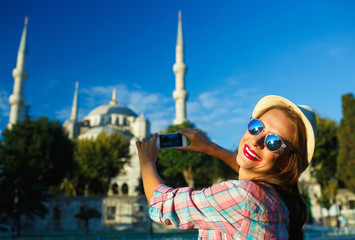 Girl making photo by the smartphone near the Blue Mosque, Istanb