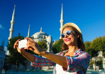 Girl making selfie by the smartphone on the background of the Bl