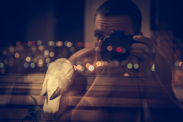 Photographer taking inspiration photograph of bird with night city lights on background. Photography concept