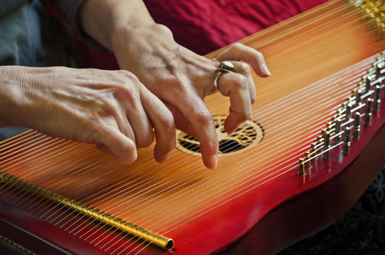 Playing music on lap harp in closeup view/Close-up of playing lap harp made out of redwood with carved tree