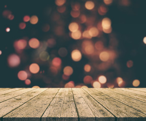 Christmas background with old wooden table against bokeh lights