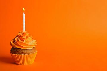 Fresh tasty cupcake with candle on orange background