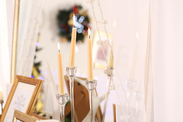 Candles and garland against mirror, close up view