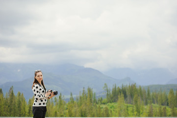 Woman photographer takes pictures in mountain
