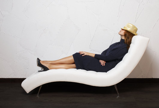businesswoman sitting on a couch. woman relaxing in a chair covering her face with a hat. indoors. the concept of six thinking hats. empty space for your text