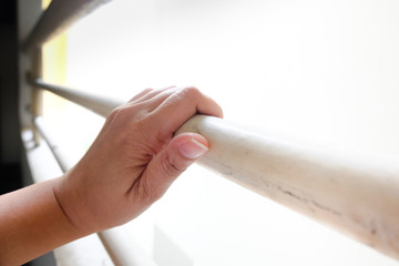 Woman hand on baluster. Photo imprison concept.