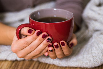 Woman with red manicure holding a red cup of tea