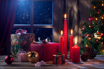 view of gift boxes and red candles on  Christmas background
