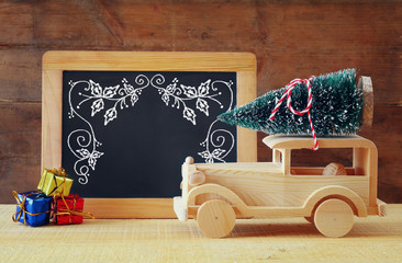 Wooden car carrying a christmas tree in front of blackboard